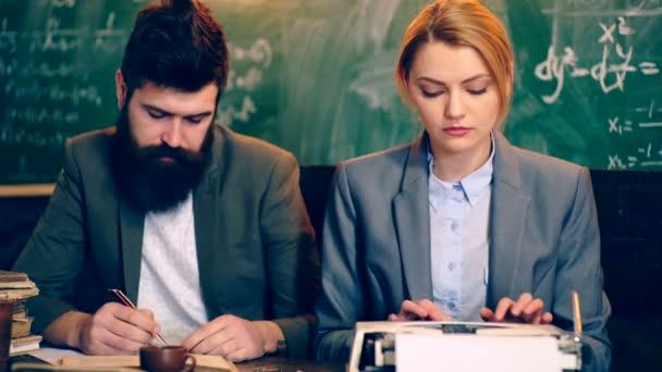 Dva učitelé zabývají papírování ve školní třídě. Koncept výuky. Školní děti v uniformě. Učitel v učebně. Učitel a student. Zpátky do školy.