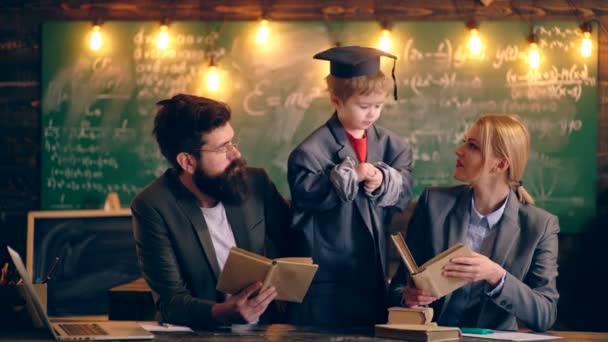 Chlapec v bundě a promoce klobouku komunikuje se dvěma učiteli, disponující knihy v pozadí školní třídy. Koncept výuky. Školní děti v uniformě. Učitel ve třídě