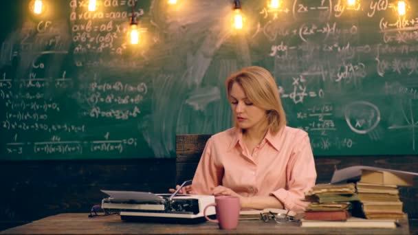 Učitel psaní textu na psacím stroji, sedět u stolu ve školní třídě na pozadí zelené desky, na nichž jsou zapsány různé vzorce. Koncept výuky