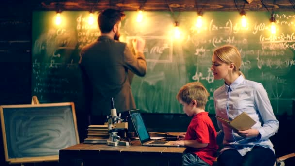 Little boy watching cartoons on a laptop with his mom sitting in a school classroom on the background of a board on which mathematics teacher wrote the formulas. Learning concept.