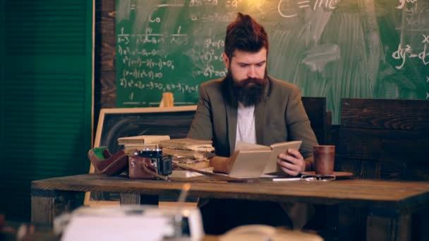 Vousatý učitel shrnuje a přečte knihu v učebně školy na pozadí zelených Rady. Koncept výuky. Školní děti v uniformě. Učitel ve třídě