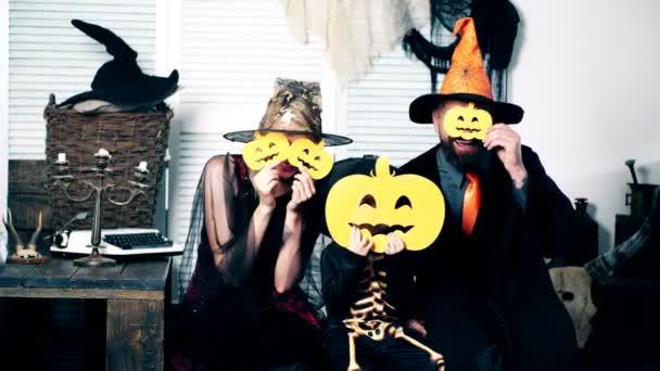 Halloween párty a oslavy koncept. Průvodce, čarodějnice a malá kostra skrýt jejich tváře za dýně. Rodina v kostýmech bavit se na halloween