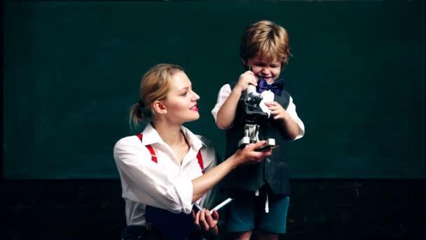 Chlapec s učitelem se dívá na mikroskopu na pozadí zelené školní rady. Koncept výuky. Školní děti v uniformě. Učitel ve třídě