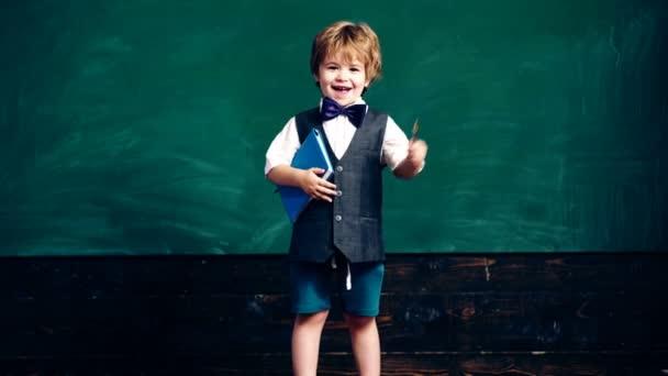 Chlapec s Poznámkový blok a pero v ruce ukazuje svůj ukazováček na pozadí zelené školní rady. Školní děti v uniformě. Učitel v učebně. Učitel a student. Zpátky do školy