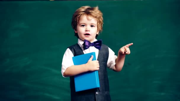 A boy in a suit holds a notebook and a pencil on the background of a green school board. Learning concept. School children in uniform. Teacher in classroom.
