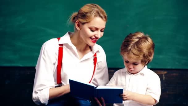 Tanító és írás egy notebook, ül egy iskolai tanteremben, a háttérben a zöld iskolaszék fiú. Tanulás-fogalom. Iskolás gyerekek egységes. Tanárnő az osztályban.