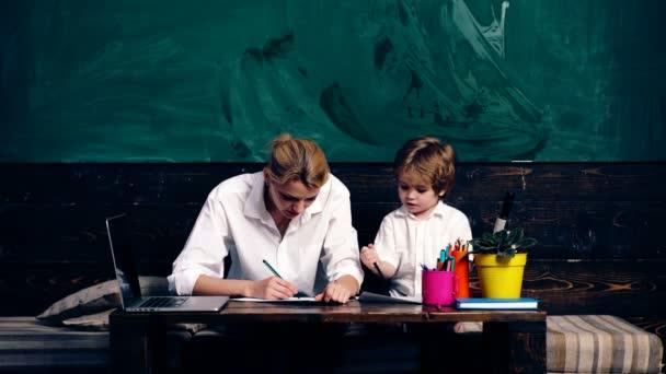 Učitel s chlapcem kreslení sedí ve školní lavici ve školní třídě na pozadí zelené školní rady. Koncept výuky. Školní děti v uniformě. Učitel v učebně. Učitel a žák.