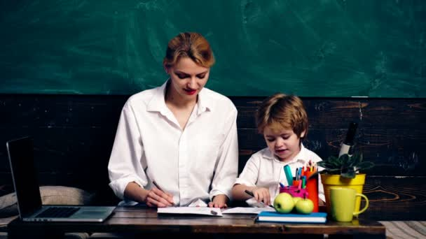 Kluk a matka oblečená v bílé košile jsou malované na pozadí zelených Rady. Koncept výuky. Školní děti v uniformě. Učitel v učebně. Učitel a student. Zpátky do školy