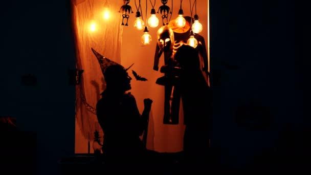 Pořád to samý. Koncept oslava Halloween. Rodina v kostýmech se bavit o Halloweenu. Silueta čarodějnice a malý drak na pozadí na halloween