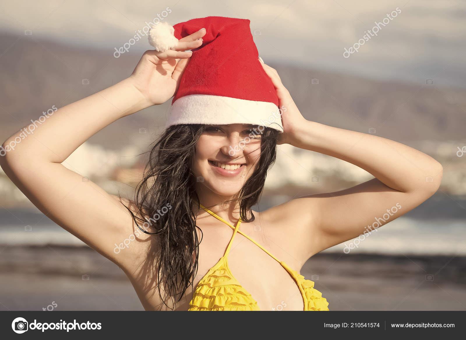 3e11516e39a3 Ευτυχισμένος κορίτσι χαμογελά στο Αϊ Βασίλη καπέλο στην παραλία της θάλασσας–  εικόνα αρχείου