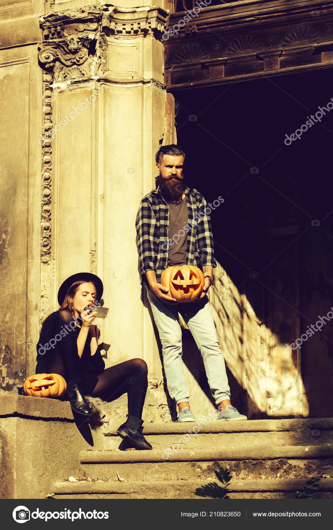 7f5c20b6fe85d Joven pareja de halloween de hombre con barba con barba y bigote y muchacha  con sombrero de bruja negro cerca de puerta de hierro del viejo arruinado  ...