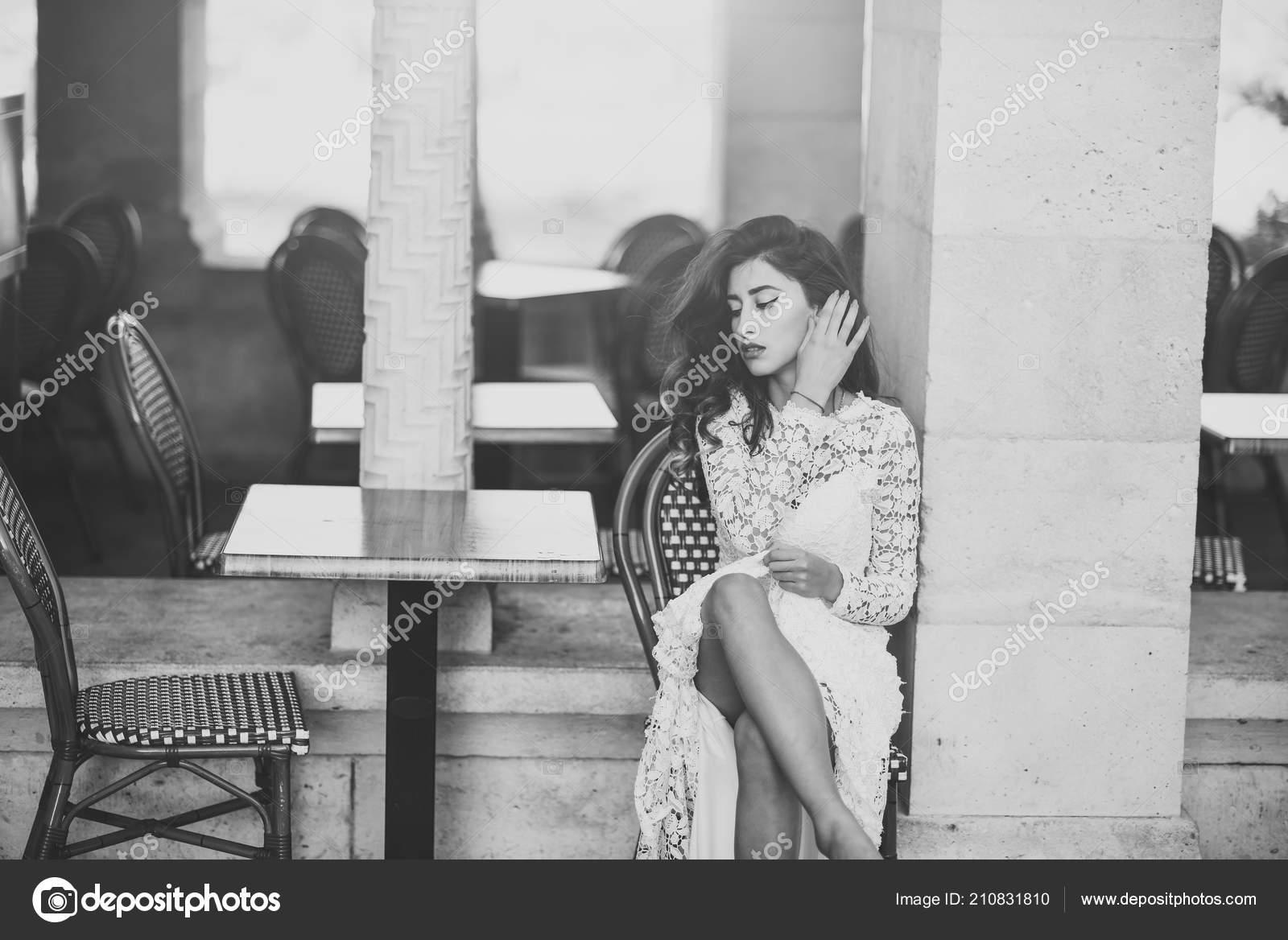 c0526dc0e17 Femme en robe blanche extérieure. Femme sexy s asseoir seul dans le café de  rue. Mannequin avec le look glamour et maquillage. Fille aux cheveux longs  brune ...