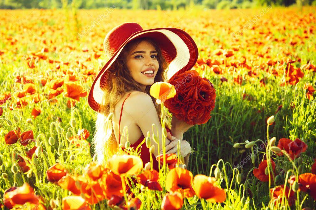 smiling girl in field of poppy seed in retro hat