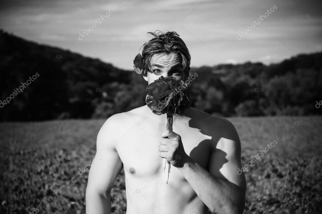 young surprised man hold bouquet of red poppy flower