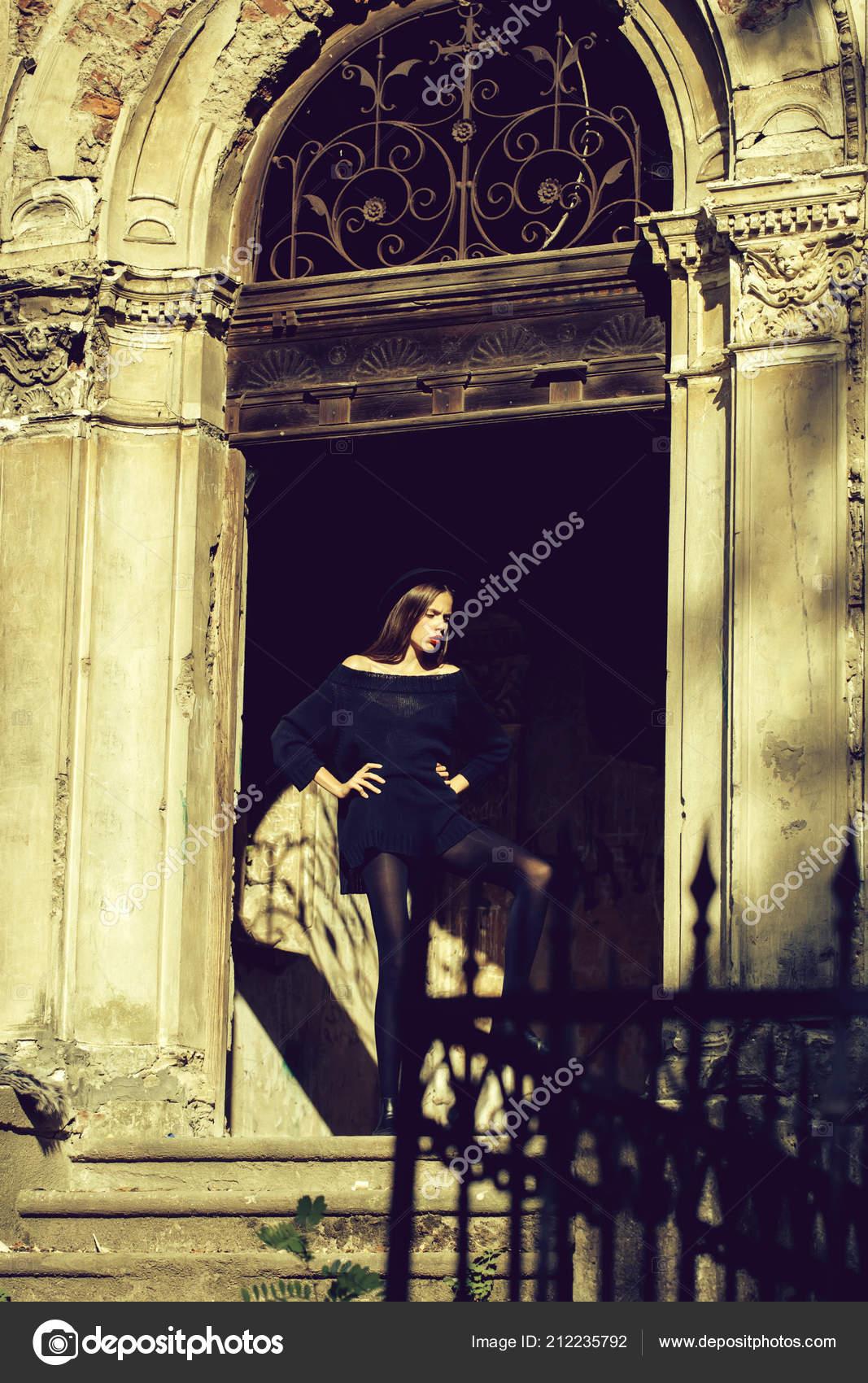 6611403547045 Moda joven mujer o chica con labios rojos en cara bonita en vestido posando  junto a la puerta de hierro de la vieja y sombrero negro arruinado edificio  ...