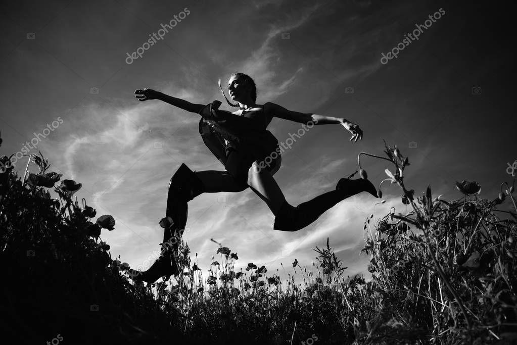 summer girl jumping in flower field of poppy seed