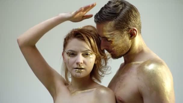 Pojetí erotiky. Mladý pár v golden make-up vzájemně dotýkají na černém pozadí. Koncept oslava Halloween. Pořád to samý.