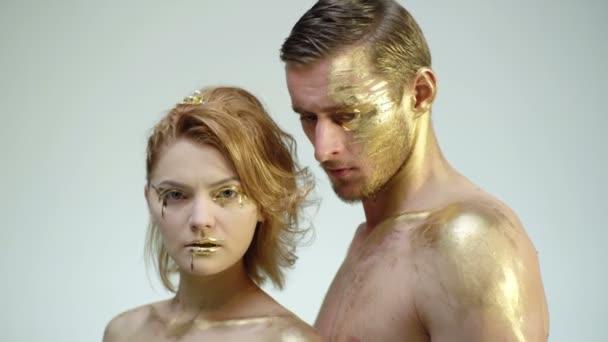 junges Paar in goldenem Make-up auf weißem Hintergrund. Erotik-Konzept. Goldener Wellnessbereich für sexy Paare mit bemaltem Körper. Halloween-Party und Festkonzept.