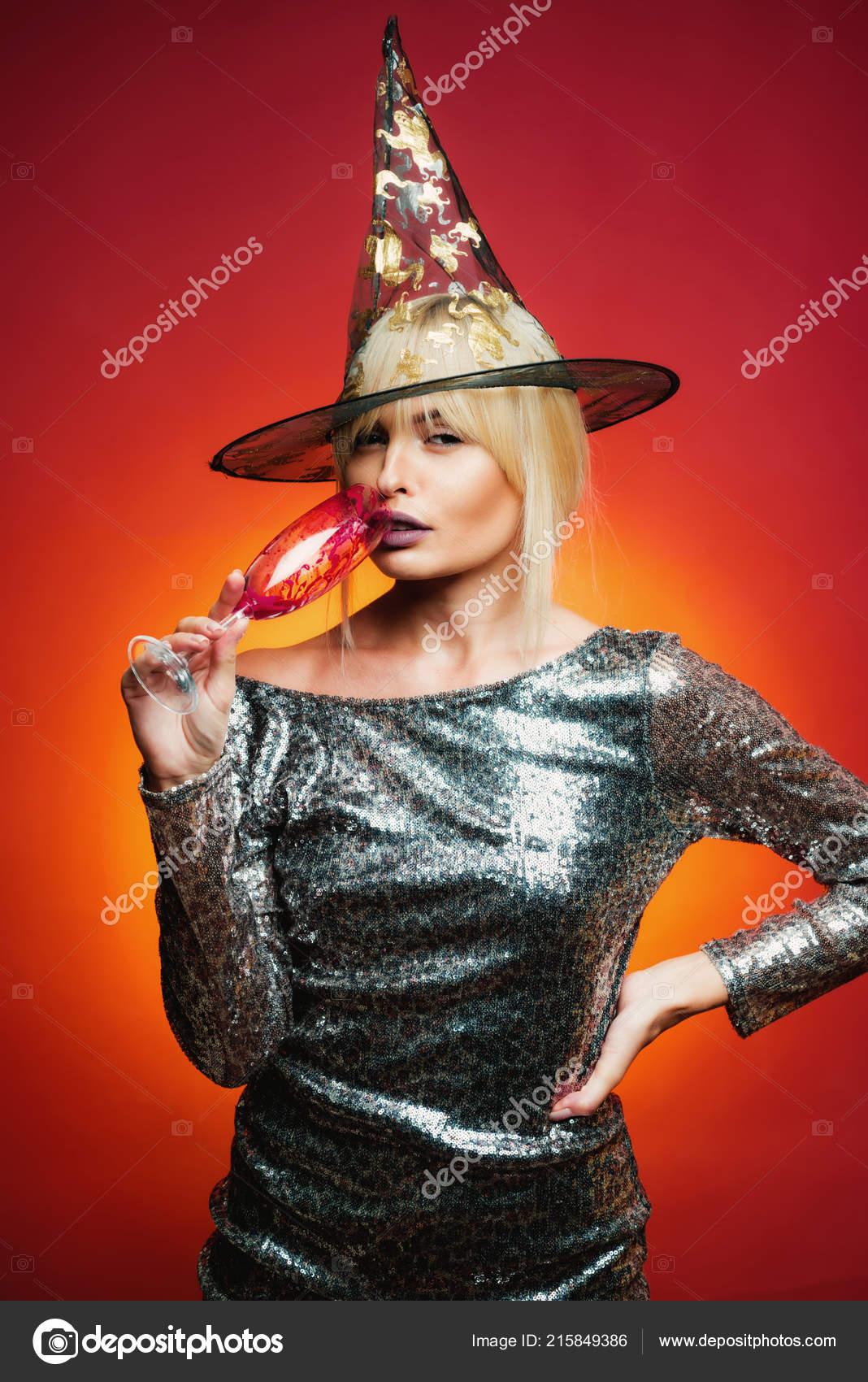 Donna sorpresa in cappello di streghe e costume su priorità bassa rossa di  Halloween. Ragazza di modello attraente in costume di Halloween. 106dd5e5c0b5