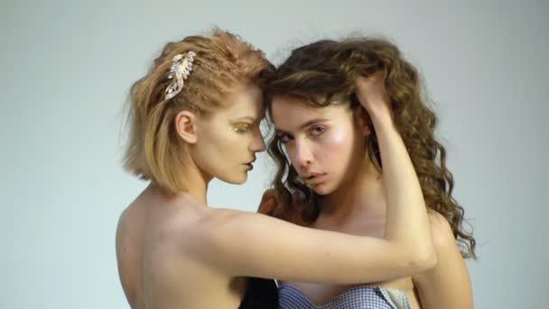 Dvě krásné dívky se zlatými make-up vzájemně dotýkají na bílém pozadí. Erotické koncept. Modelka ukazuje koncept luxusního. Vlasová kosmetika a kosmetika.