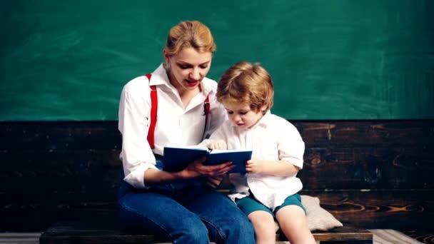 Učitel s tím malým klukem psaní v poznámkovém bloku pozadí zelené desky v učebně. Koncept výuky. Školní děti v uniformě. Učitel a student. Zpátky do školy