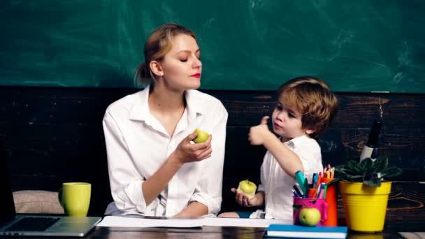 Učitel s malý chlapec jablko na žáka stůl a počítání na pozadí zelené školní rady. Koncept výuky. Učitel v učebně. Učitel a student. Zpátky do školy