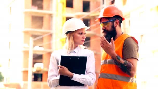 Ženské inženýr se složkou v ruce a s přilbou na hlavě komunikuje s tvůrce v ochrannou vestu na staveništi. Koncepce výstavby.