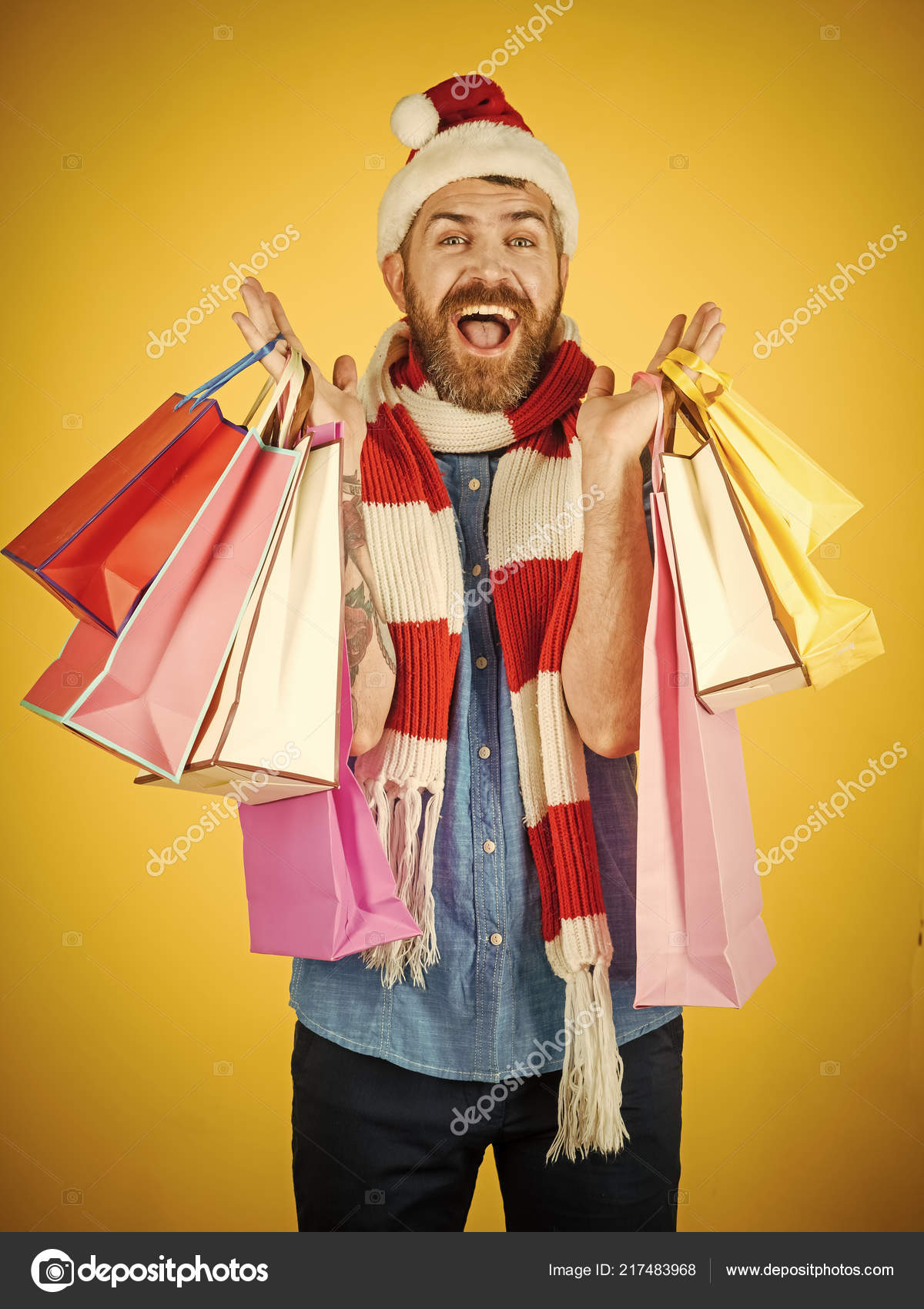 396a703a0675a Christmas man hold shopping bags on yellow background. Black friday sale  concept. Winter holidays celebration. Hipster shopper smile in santa hat  and scarf.
