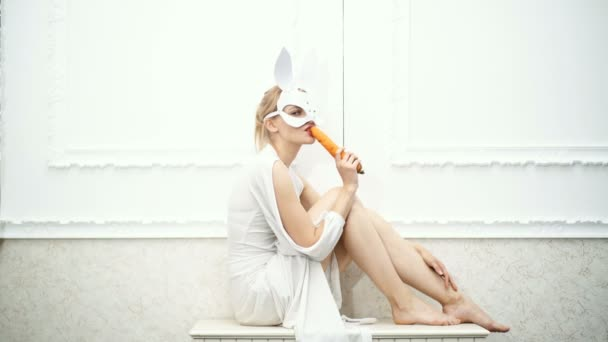 Sexy woman wearing a white mask Easter bunny standing on a white background and eating carrots. Halloween party and celebration concept.