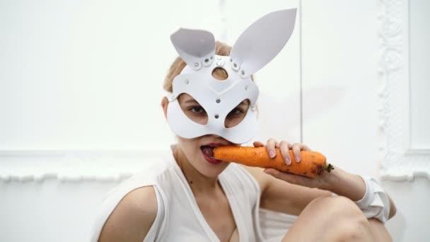 Nahaufnahme einer Frau in einer Hasenmaske, die Möhren isst. Halloween-Party und Party-Konzept. Konzept Ledermaske bdsm.