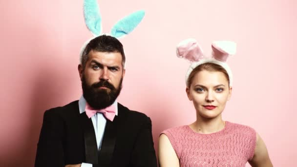 Bearded man and blond woman raising eyebrows on a pink background with ears on their heads. Concept of fashionable hare. Man and woman with hare ears on a pink background.