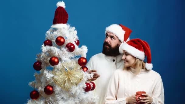 Vousatý muž a blondýna v novoroční klobouky zdobí vánoční strom na modrém pozadí. Milující pár se připravuje na oslavu nového roku. Nová let koncept.