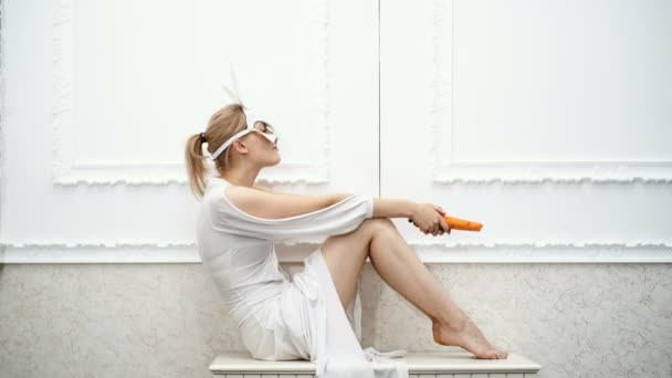 girl in white dress and in white mask of rabbit eat carrot on white background. Fashionable girl in a hare mask. Sexy Bunny Girl.