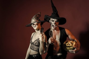 Halloween Couple in love with pumpkin and wine glass.
