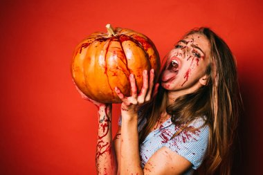 Beautiful Young woman as sexy vampire in blue dress - halloween portrait. Gory bloody and scary zombie girl. Halloween girl vampire with bloody pumpkin. Halloween zombie.