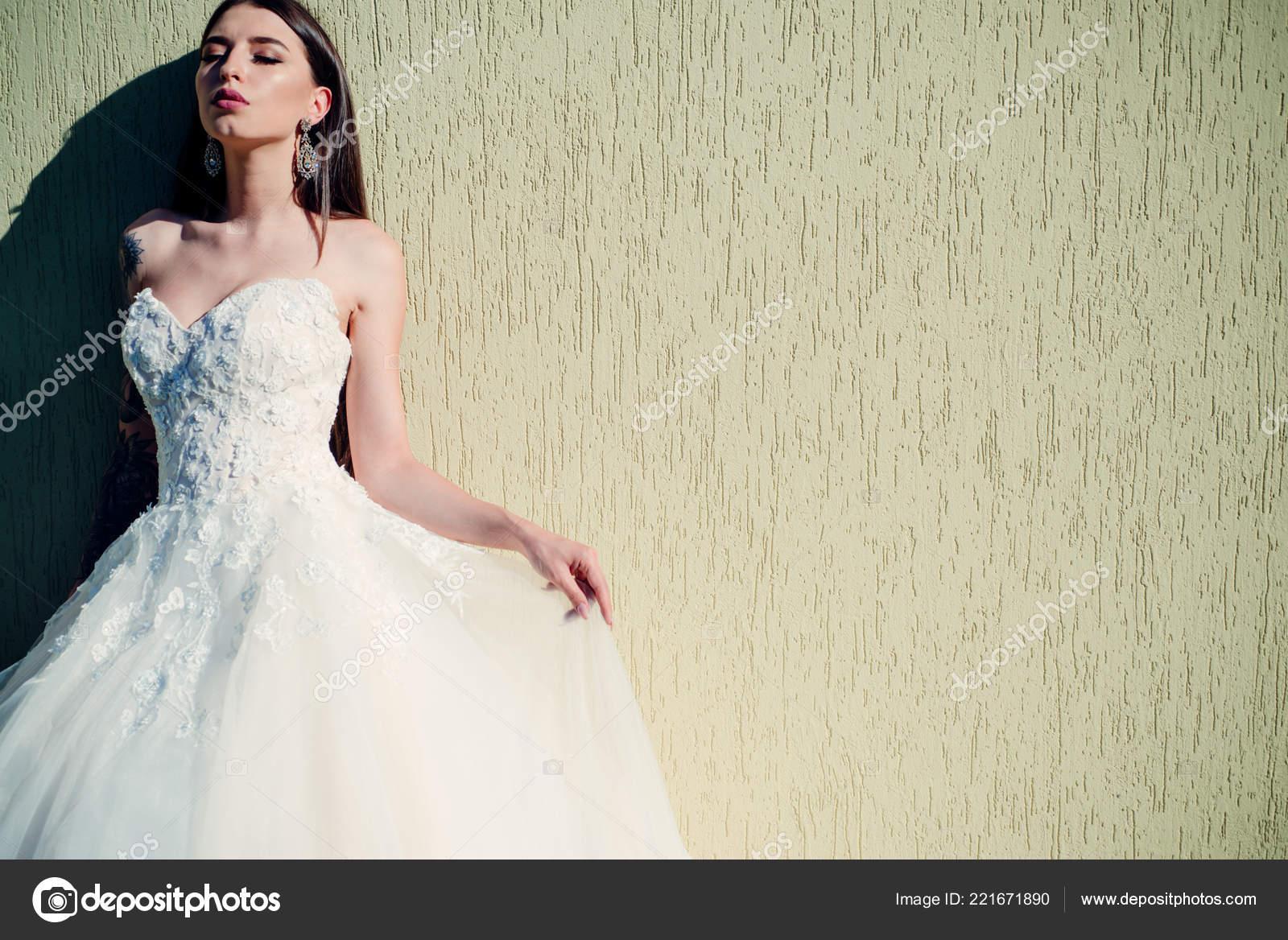 b788d1b6b0 Vestidos de boda hermosa en boutique. Maravilloso vestido de novia. mujer  se está preparando para la boda. Salon de boda elegante espera para novia