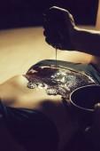 weibliche sexy Bauch und männliche Hände auf Schokoladenmassage
