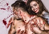 Halloween-Paar aus gutaussehendem Mann und sexy hübschem Mädchen mit langen Haaren und rotem Blut als traditionelles Herbstfest-Symbol. Sexy Frau Vampir beißt Mann in den Hals.