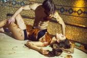 muskulöser Mann macht Schokoladenmassage für sexy Frau im Salon