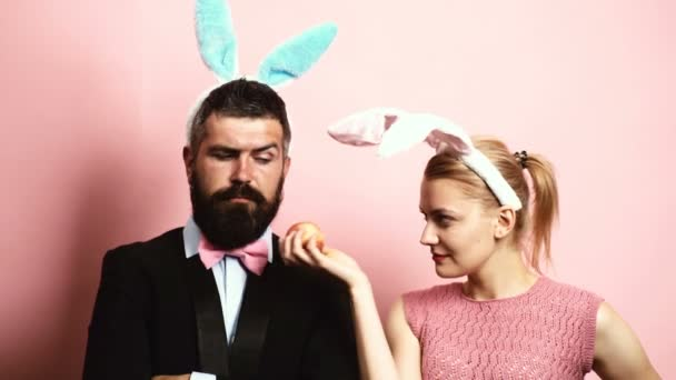 Bearded man with ears hare and blond woman with ears hare eating an apple on a pink background. A woman with rabbit ears offers an apple to her husband with rabbit ears.