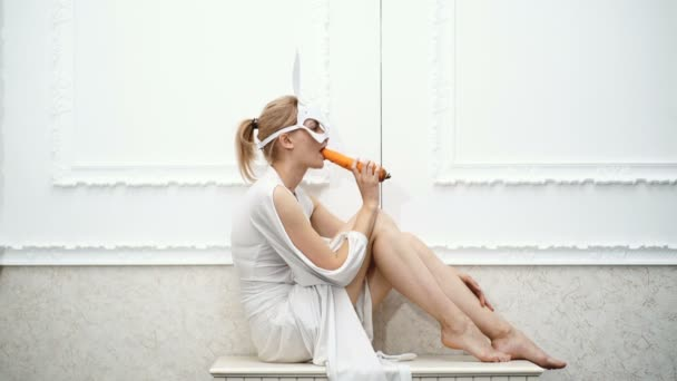 Girl dressed in a mask of a hare eating carrots on a white background. Brave woman in a mask eats carrots. Concept of modern fashion.