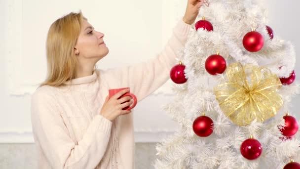 Frauen schmücken den Weihnachtsbaum. Frohe Weihnachten und ein gutes neues Jahr. Weihnachtsglühwein. Glühwein und Wintergetränke.