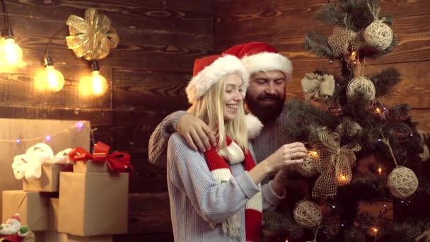 Pár ünnepli az új év party. Bemutatja a karácsonyfa alatt. Kellemes karácsonyi ünnepeket és boldog új évet. Díszíteni a karácsonyfát
