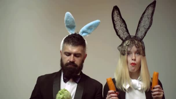 Funny rabbit couple eat carrot. Bunny ears concept with bunny couple. Heppy easter couple. Rabbit man and woman surprise emotions.