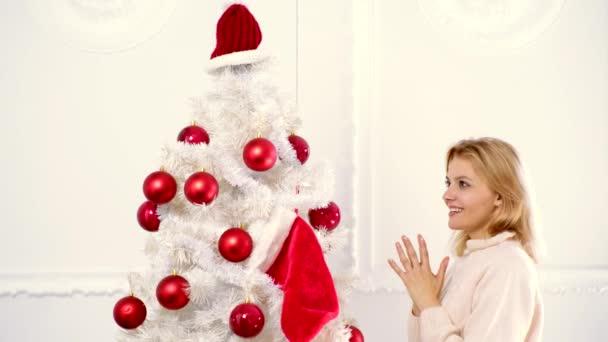 Veselé Vánoce a šťastný nový rok. Vánoční oslava, dovolená. Žena zdobení vánoční stromeček s červeným míčem doma