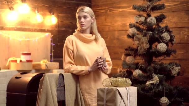 Glühweingläser mit Weihnachtsdekoration in romantischer Wohnatmosphäre. Urlaub und Menschen-Konzept - glückliches Mädchen schmückt Weihnachtsbaum zu Hause.
