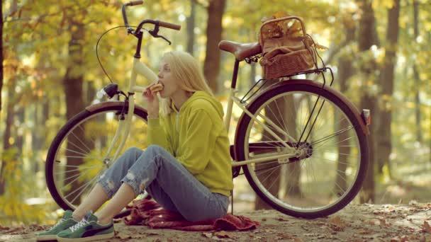 Podzimní žena v podzimním parku s zelený svetr. Žena v podzimní šaty s padající listí nad přírodní pozadí. Hudební telefon. Venkovní ovzduší v podzimní krajině.