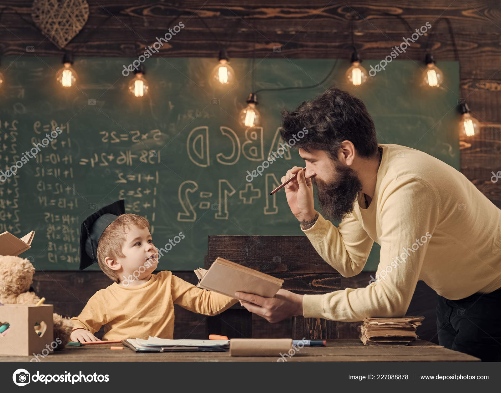 Wunderkind And Genius Concept Father Teacher Reading Book Teaching Kid Son Chalkboard On Background