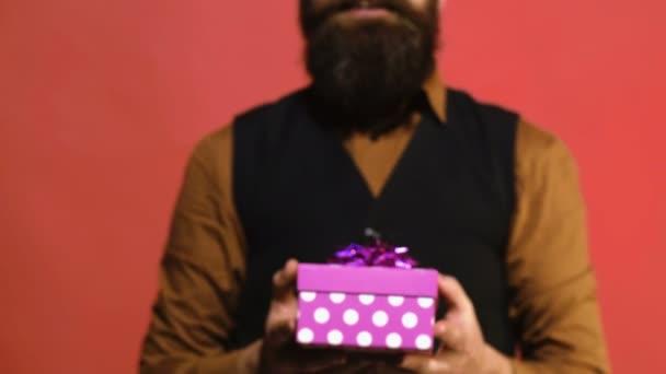Rózsaszín ajándék doboz a kezében egy férfi egy piros háttér. Az ember bemutatja egy ajándék az ünnepek. Valentin-nap-koncepció.