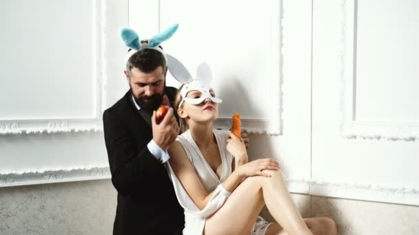 Bearded man wearing a suit and rabbit ears standing near a woman in a leather mask and eating an apple. Fashionable pair in rabbit masks on a white background.